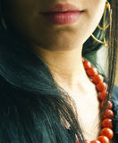 Beautiful girl with red beads. Beautiful brunette young girl with red glass-beads close-up neck and lips Royalty Free Stock Photos