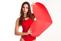 Beautiful girl in red bodi holding big paper heart. Pretty slim teenager girl is wearing red sexy bodi holding red big paper hearts over white background Royalty Free Stock Image