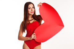 Beautiful girl in red bodi holding paper heart. Pretty teen girl is wearing red bodi holding big red paper heart over white background, valentines day Royalty Free Stock Images