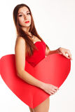 Beautiful girl in red bodi holding paper heart. Pretty teenager brunette girl is wearing red bodi holding red big paper hearts over white background, valentines Royalty Free Stock Photo