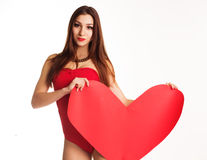 Beautiful girl in red bodi holding paper heart. Pretty teenager girl is wearing red bodi holding red big paper hearts over white background, valentines day Stock Photography