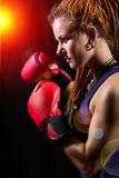 Beautiful girl with red boxing gloves, dreadlocks on a black bac Stock Photo