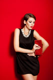 Beautiful girl with a red clutch bag Royalty Free Stock Images