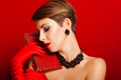 Beautiful girl with a red clutch bag Royalty Free Stock Photography