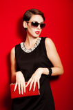Beautiful girl with a red clutch bag in her hands Stock Image