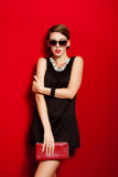 Beautiful girl with a red clutch bag in her hands Stock Photography