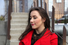 Beautiful girl in a red coat on the background of the stairs royalty free stock photography