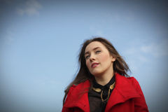 Beautiful girl in a red coat on a blue sky background Stock Photography