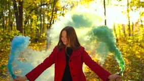 Beautiful girl in a red coat holds colored smoke in her hands and walks through the yellow autumn forest. Weekend outside the city stock video footage
