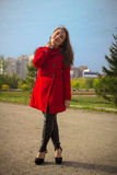 Beautiful girl in a red coat on a park alley Stock Image