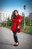 Beautiful girl in a red coat on a park alley stock images