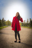Beautiful girl in a red coat on a park alley Royalty Free Stock Image