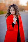 Beautiful girl in red coat standing on the road Stock Photos