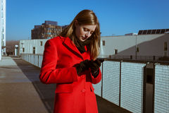 Beautiful girl with red coat using phone Stock Image
