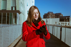 Beautiful girl with red coat using phone Stock Photos