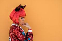 Beautiful girl in red devil costume standing against the wall in anticipation of Halloween. Wears a red wig and horns Stock Photos
