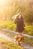 Beautiful girl with a red dog goes under the rays of the sun stock photo
