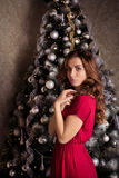 Beautiful girl in red dress on the Christmas tree Royalty Free Stock Images