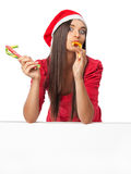 Beautiful girl in a red dress eating candy cane Royalty Free Stock Images