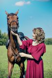 A beautiful girl in a red dress and her horse. A beautiful girl in a red dress is feeding a brown horse stock photos