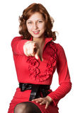Beautiful girl in a red dress in front indicates a finger Stock Images