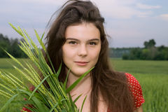Beautiful girl in red dress in green wheat field Royalty Free Stock Photo