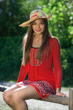 Beautiful girl in a red dress and a hat Royalty Free Stock Photos