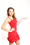 Beautiful girl in a red dress holding, makes palm up isolated Stock Photos