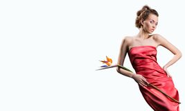 Beautiful girl in red dress holds exotic flower Royalty Free Stock Images