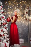 Beautiful girl in red dress, is meeting Christmas at the New Year tree. New Year. Christmas Royalty Free Stock Photo
