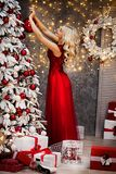 Beautiful girl in red dress, is meeting Christmas at the New Year tree. New Year. Christmas Stock Photography