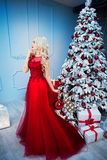 Beautiful girl in red dress, is meeting Christmas at the New Year tree. New Year. Christmas Stock Images