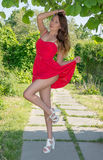 Beautiful girl in a red dress relax and fool around Stock Photography