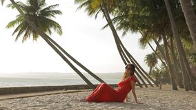 Beautiful girl in red dress is relaxing on the beach under palm trees. stock footage