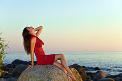 Beautiful girl on seacoast before a sunset Royalty Free Stock Image