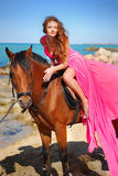 The beautiful girl in red dress sits on horse. On beach Royalty Free Stock Image