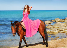 The beautiful girl in red dress sits on horse. On beach Royalty Free Stock Images