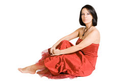 Beautiful girl in red dress sitting Stock Photography