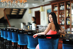 Beautiful girl in red dress sitting at the bar in the restaurant Royalty Free Stock Photos