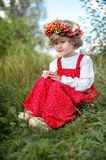 Beautiful girl in red dress sitting on the grass with a branch o Stock Photography
