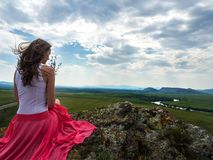 Beautiful girl in red dress sitting on a rock at the top of the mountains. Stock Photos