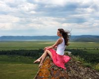 Beautiful girl in red dress sitting on a rock at the top of the mountains. Royalty Free Stock Image