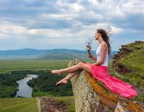 Beautiful girl in red dress sitting on a rock at the top of the mountains. He holds a bouquet of flowers in his hand. stock photography