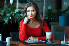 Beautiful girl in red dress sitting and smiling. Royalty Free Stock Photography