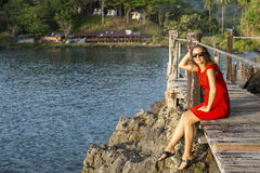 Beautiful girl in red dress sitting on the wooden bridge over the Bay Stock Photography