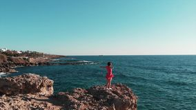 Beautiful girl in red dress standing on rocky cliff. Young girl standing on rocky beach with hands apart. Girl in short dress look stock video footage