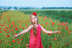 Beautiful girl in red dress walks at poppy field Stock Photography