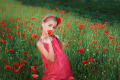 Beautiful girl in red dress walks at poppy field.  Royalty Free Stock Images
