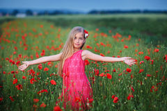 Beautiful girl in red dress walks at poppy field.  Stock Image