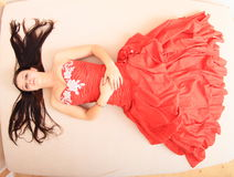 Beautiful girl in red evening dress on bed Royalty Free Stock Photo